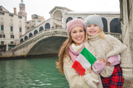 grand child: Modern family taking a winter break to enjoy inspirational adventure in Venice, Italy. Happy mother and daughter holding Italian flag while standing in front of Rialto Bridge Stock Photo