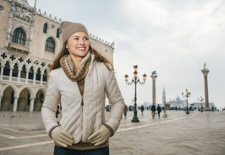looking aside: Delightful Venice, Italy can help make the most of your next winter getaway. Happy young woman tourist standing on St. Marks Square near Dogi Palace and looking aside