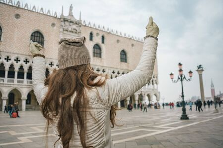rejoicing: Delightful Venice, Italy can help make the most of your next winter getaway. Seen from behind young woman tourist rejoicing on St. Marks Square near Dogi Palace Stock Photo