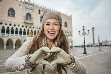shaped hands: Delightful Venice, Italy can help make the most of your next winter getaway. Smiling young woman tourist showing heart shaped hands on St. Marks Square near Dogi Palace