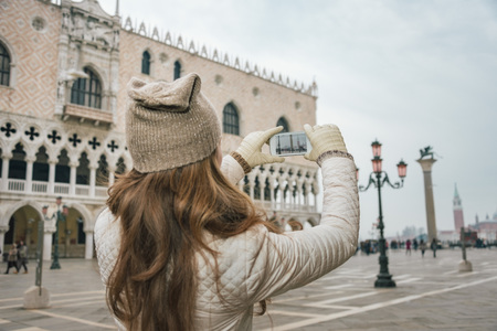 winter photos: Delightful Venice, Italy can help make the most of your next winter getaway. Seen from behind young woman tourist taking photos on St. Marks Square near Dogi Palace