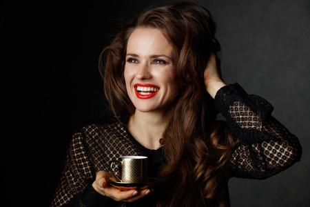 Je kan niet mis gaan met een kopje barista maakte een goede Italiaanse koffie. Glimlachende vrouw met lang golvend bruin haar en rode lippen houden kopje koffie op een donkere achtergrond Stockfoto