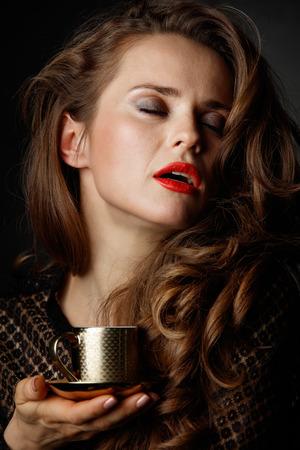 Je kan niet mis gaan met een kopje barista maakte een goede Italiaanse koffie. Sluit portret van vrouw met lang golvend bruin haar en rode lippen genieten van een kopje koffie tegen een donkere achtergrond Stockfoto