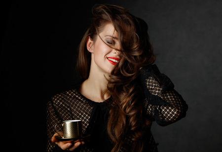 Je kan niet mis gaan met een kopje barista maakte een goede Italiaanse koffie. Gelukkige vrouw met lang golvend bruin haar en rode lippen houden kopje koffie op een donkere achtergrond
