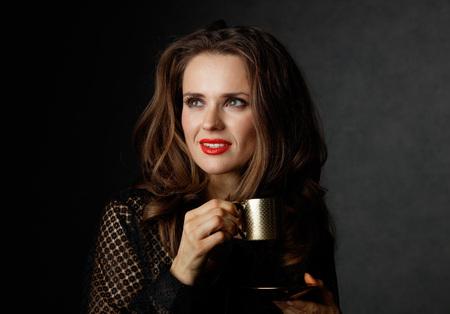 Je kan niet mis gaan met een kopje barista maakte een goede Italiaanse koffie. Vrouw met lang golvend bruin haar en rode lippen houden kopje koffie en op zoek op kopie ruimte op een donkere achtergrond Stockfoto