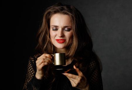 Je kan niet mis gaan met een kopje barista maakte een goede Italiaanse koffie. Portret van gelukkige vrouw met lang golvend bruin haar en rode lippen genieten van een kopje koffie tegen een donkere achtergrond
