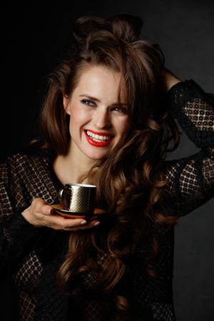 Je kan niet mis gaan met een kopje barista maakte een goede Italiaanse koffie. Portret van vrolijke vrouw met lang golvend bruin haar en rode lippen houden kopje koffie op een donkere achtergrond