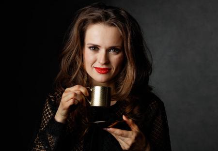 Je kan niet mis gaan met een kopje barista maakte een goede Italiaanse koffie. Portret van een vrouw met lang golvend bruin haar en rode lippen houden kopje koffie tegen een donkere achtergrond
