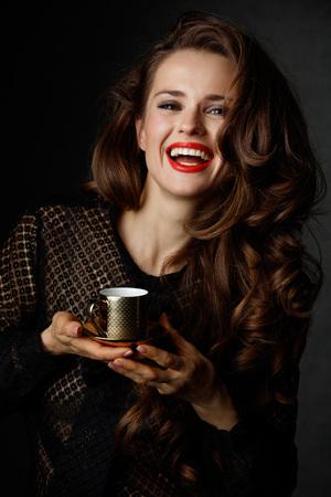 Je kan niet mis gaan met een kopje barista maakte een goede Italiaanse koffie. Portret van glimlachende vrouw met lang golvend bruin haar en rode lippen houden kopje koffie op een donkere achtergrond