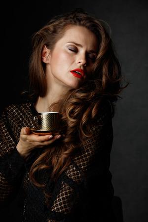 Je kan niet mis gaan met een kopje barista maakte een goede Italiaanse koffie. Vrouw met lang golvend bruin haar en rode lippen genieten van een kopje koffie tegen een donkere achtergrond