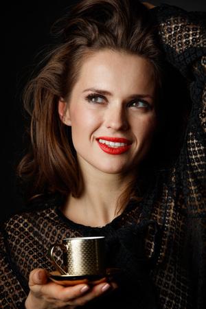 Je kan niet mis gaan met een kopje barista maakte een goede Italiaanse koffie. Portret van gelukkige vrouw met lang golvend bruin haar en rode lippen houden kopje koffie tegen een donkere achtergrond