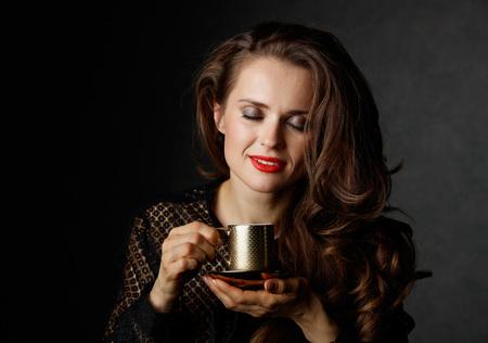 Je kan niet mis gaan met een kopje barista maakte een goede Italiaanse koffie. Gelukkige vrouw met lang golvend bruin haar en rode lippen genieten van een kopje koffie tegen een donkere achtergrond