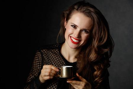 Je kan niet mis gaan met een kopje barista maakte een goede Italiaanse koffie. Portret van glimlachende vrouw met lang golvend bruin haar en rode lippen houden kopje koffie tegen een donkere achtergrond