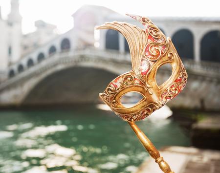 Último acceso directo escapada - iniciar Año Nuevo pasando Carnaval en Venecia, Italia. Primer en la mano de mujer con máscara de Venecia en la parte delantera del puente de Rialto