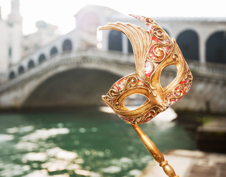 Ultimate getaway shortcut - start New Year going on Carnival in Venice, Italy. Closeup on woman hand holding Venice Mask in the front of Rialto Bridge Stockfoto