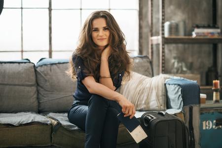 путешествие: Начинка Вдохновение для приключений! Улыбаясь элегантная женщина с паспортом, билет и багаж, сидя на диване в квартире чердак, ожидая вылета. С праздником и путешествия концепции