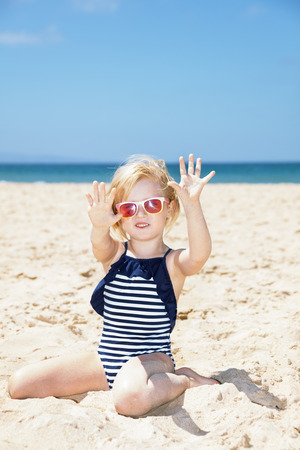 summery: Fun on white sand. Happy girl in striped swimsuit on a white beach showing sandy hands Stock Photo