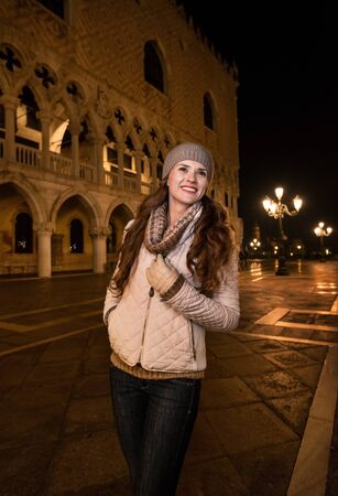 Evening promenade in Venice take you into another world. Portrait of smiling young woman tourist standing.