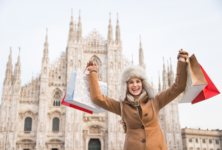 rejoicing: Discovering Italian treasures hidden in Milan. Happy woman with shopping bags rejoicing in the front of Duomo Stock Photo