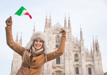 rejoicing: Discovering Italian treasures hidden in Milan. Happy woman tourist with Italian flag rejoicing in the front of Duomo
