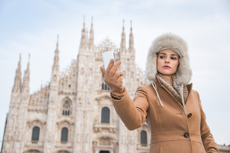 discovering: Discovering Italian treasures hidden in Milan. Woman taking selfie with smartphone while standing in the front of Duomo Stock Photo