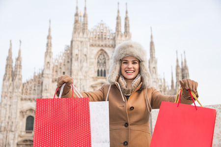 discovering: Discovering Italian treasures hidden in Milan. Smiling woman showing shopping bags in the front of Duomo