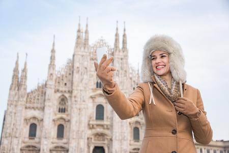 discovering: Discovering Italian treasures hidden in Milan. Smiling woman traveller taking selfie with smartphone while standing in the front of Duomo