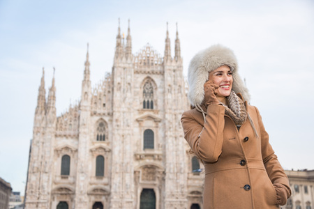 discovering: Discovering Italian treasures hidden in Milan. Happy woman talking smartphone while standing in the front of Duomo