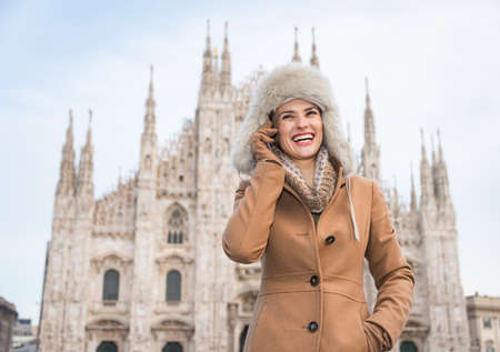 discovering: Discovering Italian treasures hidden in Milan. Smiling woman tourist talking cell phone while standing in the front of Duomo