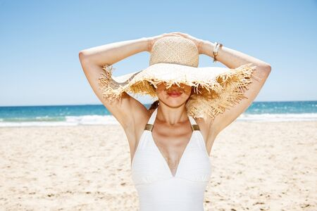 Heading to white sand blue sea paradise. Smiling woman in white swimsuit hiding under big straw hat at sandy beach on a sunny day