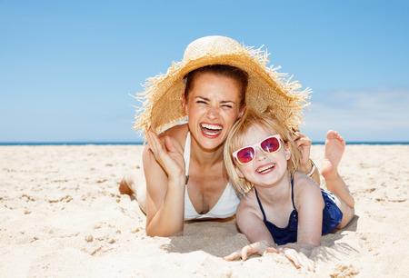 traje de bano: diversi�n de la familia en la arena blanca. Retrato de la madre y la hija sonriente en traje de ba�o que pone en la playa de arena en un d�a soleado en virtud del gran sombrero de paja