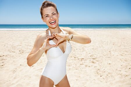 shaped hands: Heading to white sand blue sea paradise. Happy woman in white swimsuit showing heart shaped hands at sandy beach on a sunny day