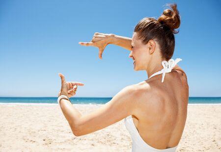 traje de bano: La partida de arena blanca del para�so azul del mar. Mujer feliz en traje de ba�o blanco en la playa de arena en un d�a soleado que enmarca con las manos Foto de archivo