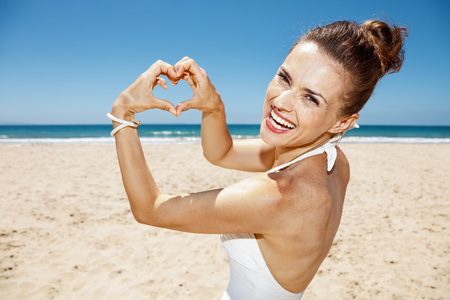 shaped hands: Heading to white sand blue sea paradise. Smiling woman in white swimsuit showing heart shaped hands at sandy beach on a sunny day