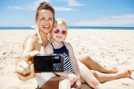 children swimsuit: Family fun on white sand. Happy mother and child in swimsuits taking selfies with digital camera at sandy beach on a sunny day
