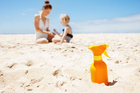 children swimsuit: Family fun on white sand. Closeup on sunscreen bottle at sandy beach on a sunny day. Mother and child in swimsuits playing in background