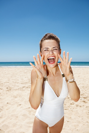 shaped hands: Heading to white sand blue sea paradise. Happy woman in white swimsuit shouting through megaphone shaped hands at sandy beach on a sunny day