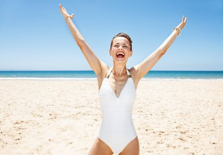 rejoicing: Heading to white sand blue sea paradise. Happy woman in white swimsuit at sandy beach on a sunny day rejoicing
