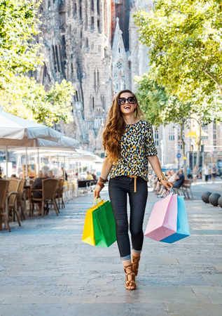 Getting unique trends of Barcelona. Full length portrait of happy fashion-monger woman with shopping bags walking down the street