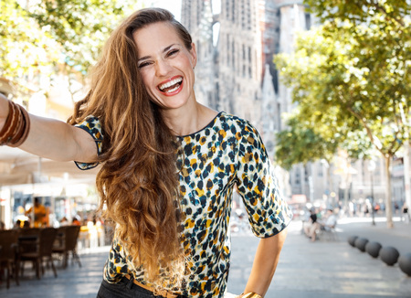 gaudy: Get ready to exciting weekend at Barcelona. Smiling woman tourist taking selfie Stock Photo