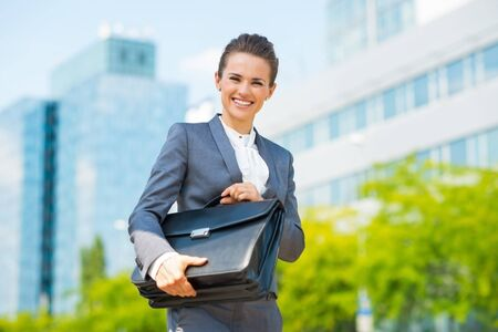 business trends: Into the ultra-modern business trends. Portrait of smiling business woman in modern office district holding briefcase