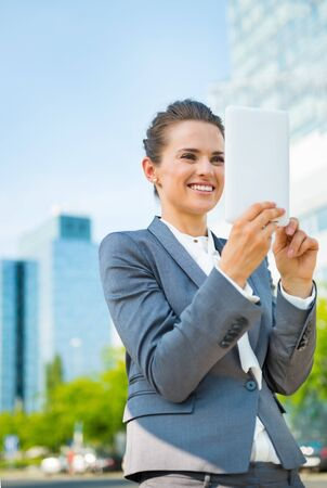 topicality: Into the ultra-modern business trends. Smiling business woman using tablet PC in modern office district Stock Photo