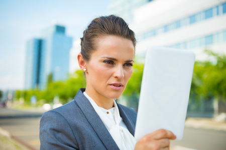 topicality: Into the ultra-modern business trends. Business woman using tablet PC in modern office district Stock Photo