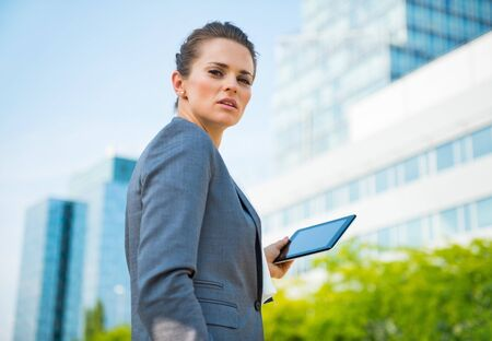 topicality: Into the ultra-modern business trends. Portrait of business woman with tablet PC in modern office district Stock Photo