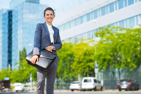 business trends: Into the ultra-modern business trends. Portrait of happy business woman holding briefcase while standing in modern office district