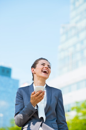business trends: Into the ultra-modern business trends. Portrait of laughing business woman with smartphone in modern office district