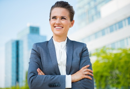 business trends: Into the ultra-modern business trends. Smiling business woman in modern office district looking into the distance