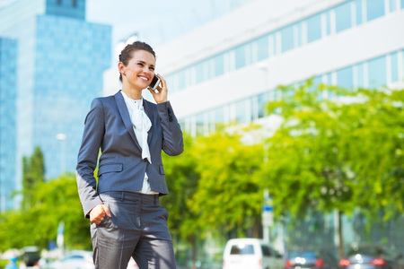 business trends: Into the ultra-modern business trends. Happy business woman in modern office district talking cellphone Stock Photo
