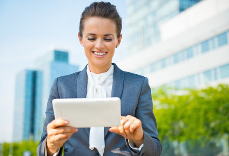 business trends: Into the ultra-modern business trends. Smiling business woman using tablet PC in modern office district Stock Photo