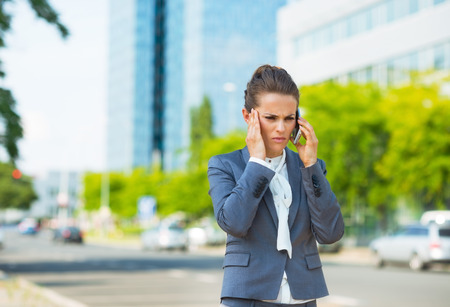 business trends: Into the ultra-modern business trends. Stressed business woman in modern office district talking smartphone Stock Photo
